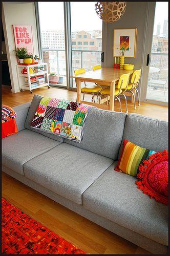 sofa cinza e cadeiras brancas