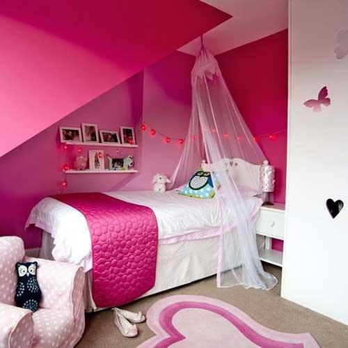 Quarto de menina rosa e branco com paredes decoradas