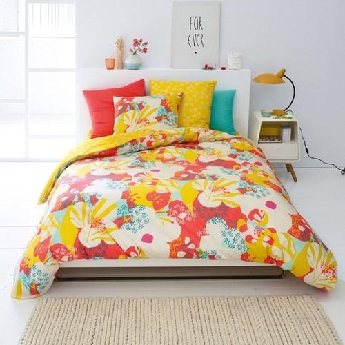 Quarto pequeno para casal com flores na roupa de cama