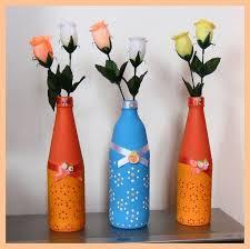 Garrafas decoradas com cores diferentes e com duas flores cada