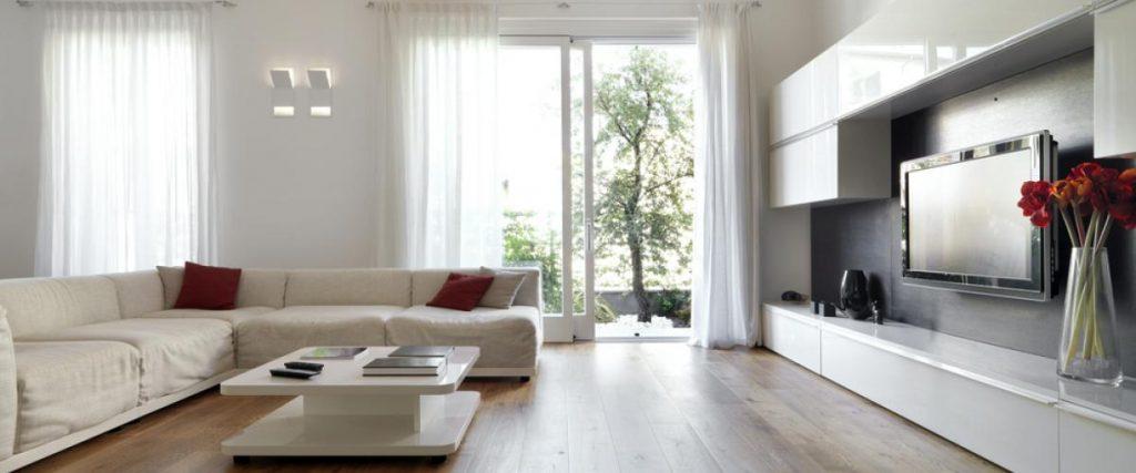 Grande porta externa de correr transparente com cortinas brancas