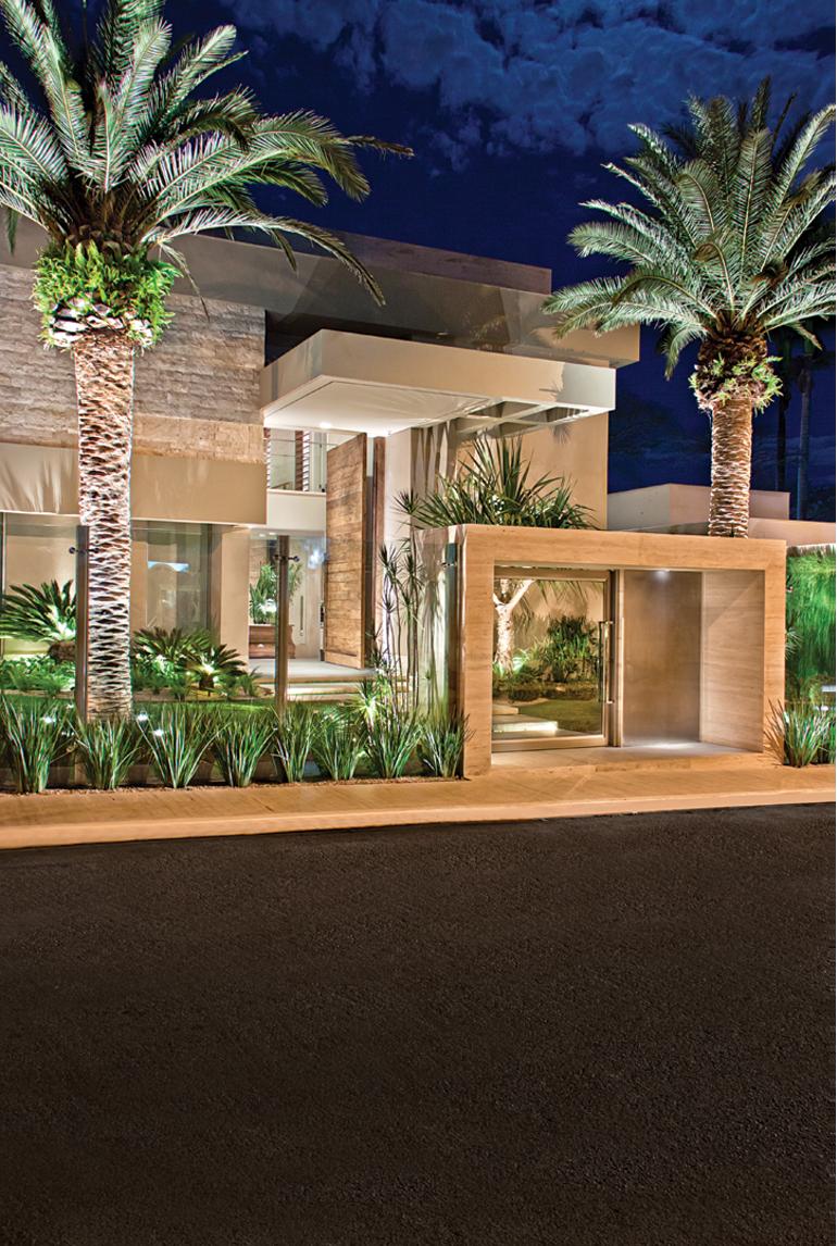 Casa elegante com coqueiros ilumninados