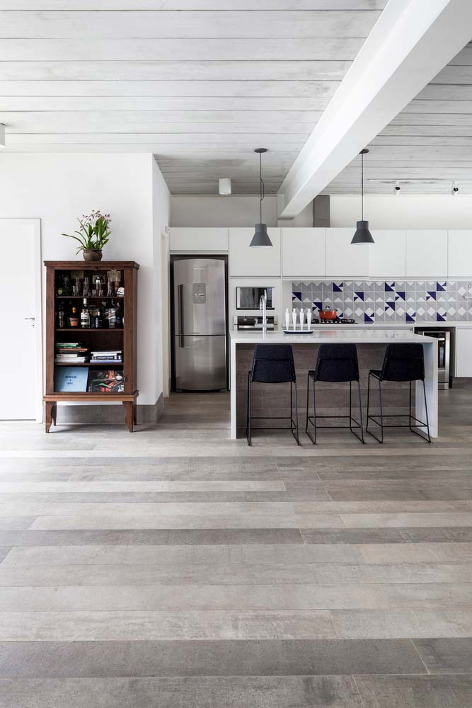 Porcelanato claro imitando madeira em uma sala integrada com a cozinha