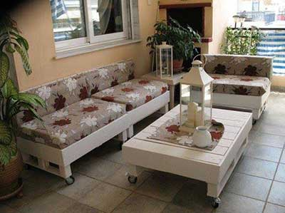 almofadas floridas no banco de pallet posto na varanda
