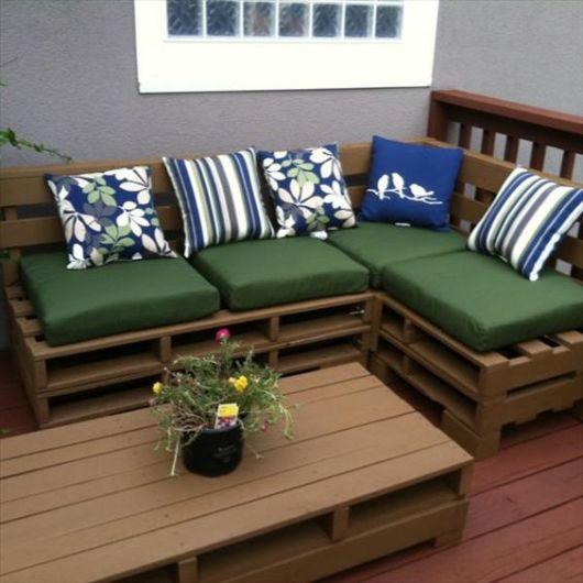 banco de pallet com almofadas verdes na varanda