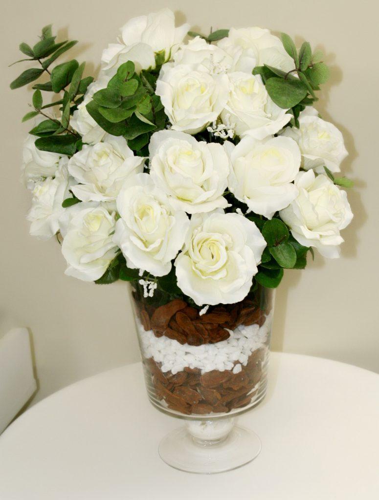 Rosas brancas com fundo do vaso em pedras