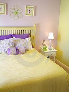 Cama em amarelo e parede em lilás claro no quarto