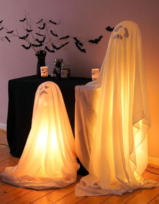 Decoração de halloween com fantasmas de lençol e luzes