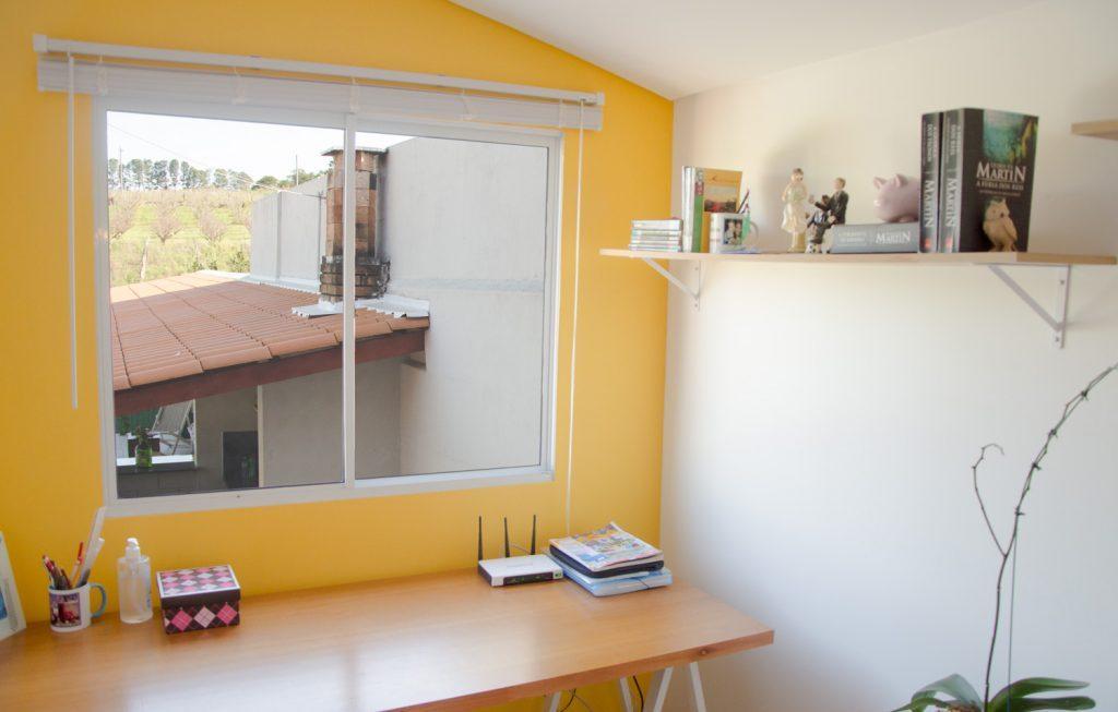 Janela com persiana em uma parede amarela no seu quarto
