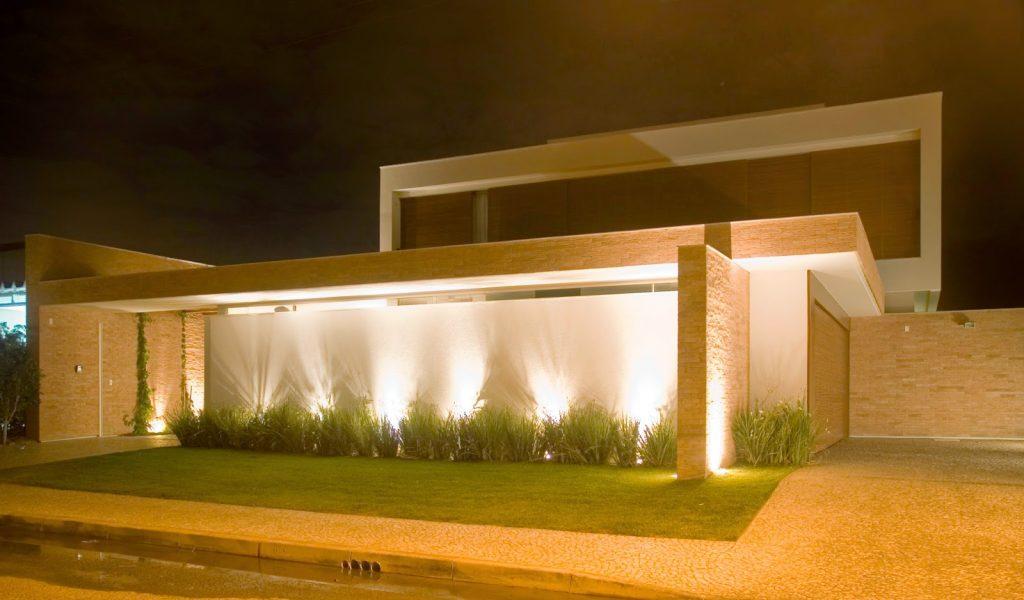 Jardim com muro na frente de casa com luzes para cima