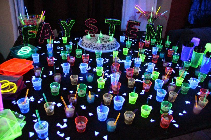 Linda mesa de festa com decoração iluminada por neon