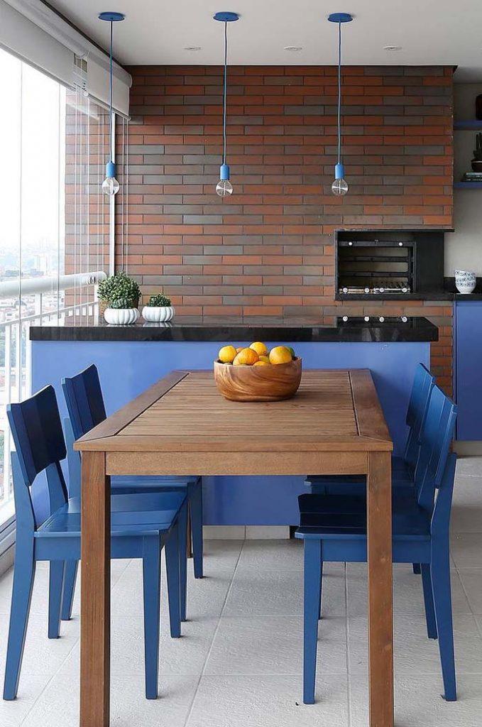 Mesa feita com madeira semi clareada na varanda