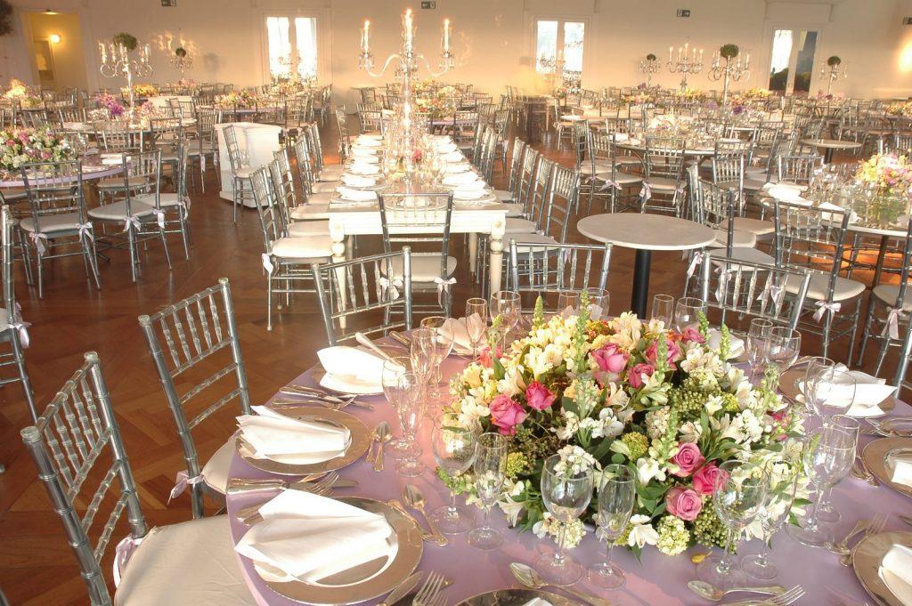 Mesas de festa de casamento iluminadas com casticais