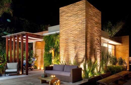 Muro da frente do jardim iluminado por luzes