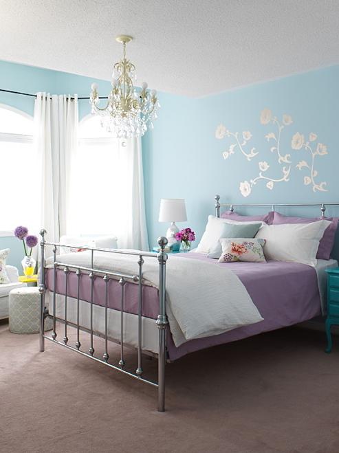 Parede azul com roupa de cama em lilás na decoração do quarto