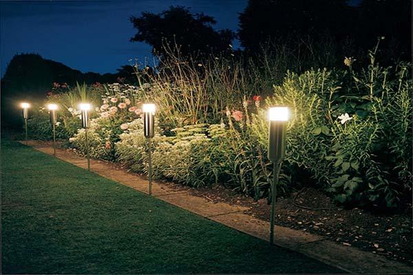 Postes em formato de tochas iluminando o jaridm
