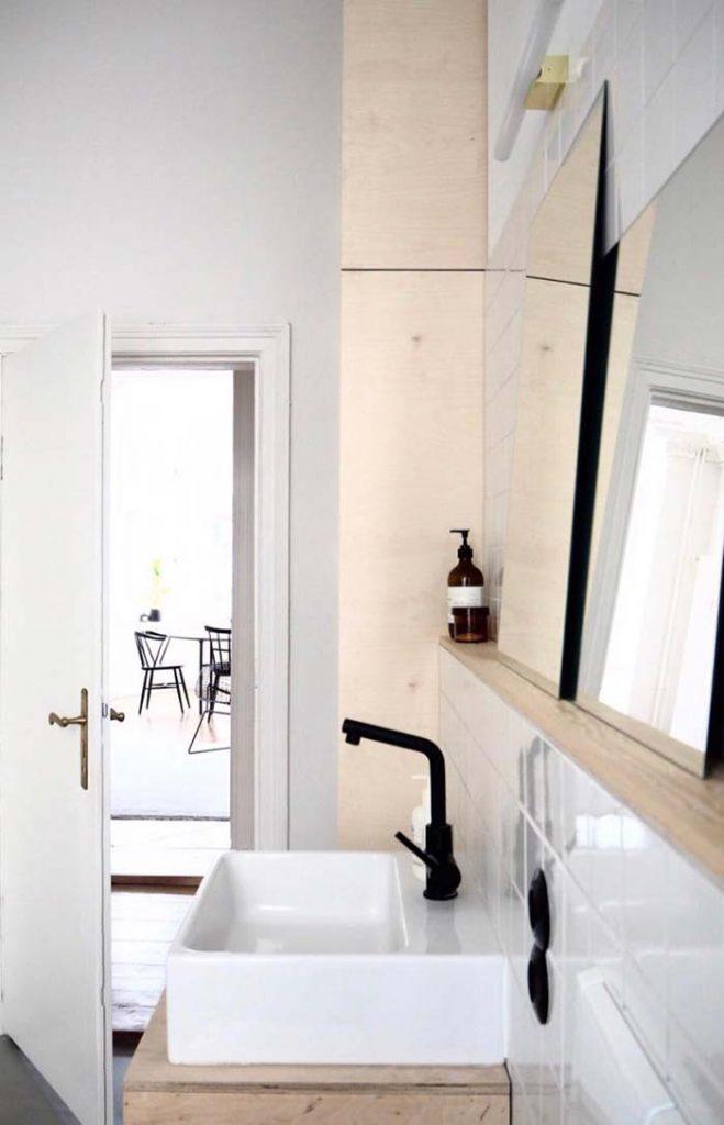 madeira com um tom puxado pro branco nos móveis do banheiro