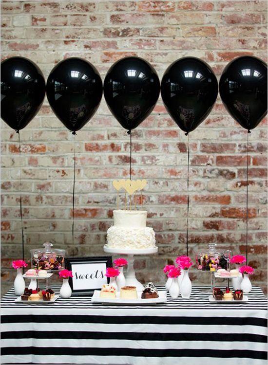 Balões pretos flutuantes com mesa listrada em preto e branco