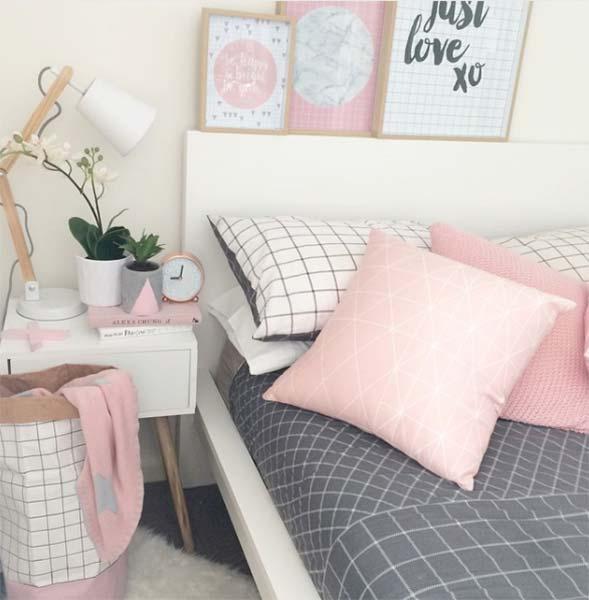 Cama com lençol cinza e almofadas rosas