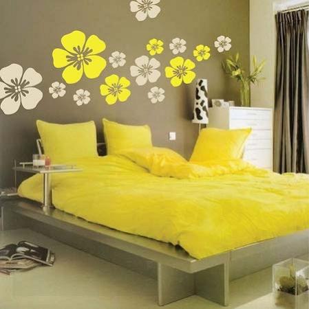 Cama no quarto amarelo com floers amarelas na parede