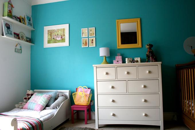 Detalhes em amarelo no quarto e parede azul marinho