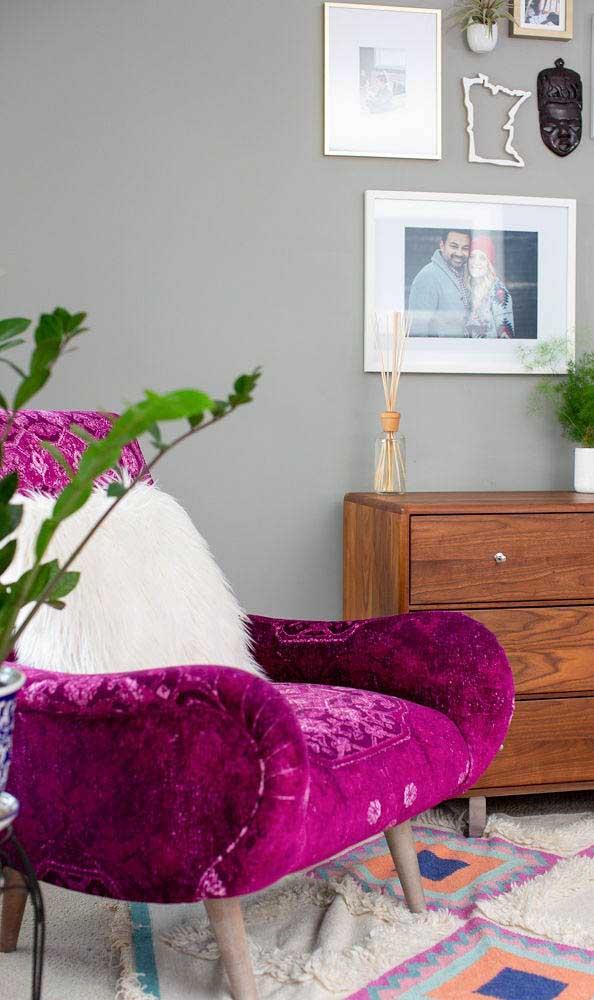 Fucsia na poltrona da sua sala de estar com móveis em madeira do lado