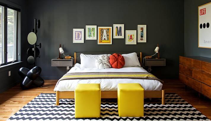 Parede em cinza forte e pufs amarelos na beira da cama
