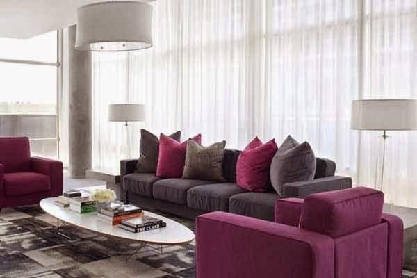 Poltroa e almofadas em fucsia na decoração da sala de estar