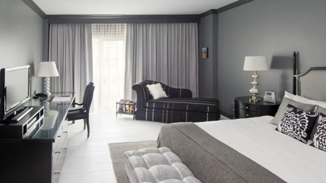 Quarto branco com paredes e móveis cinza no seu canto