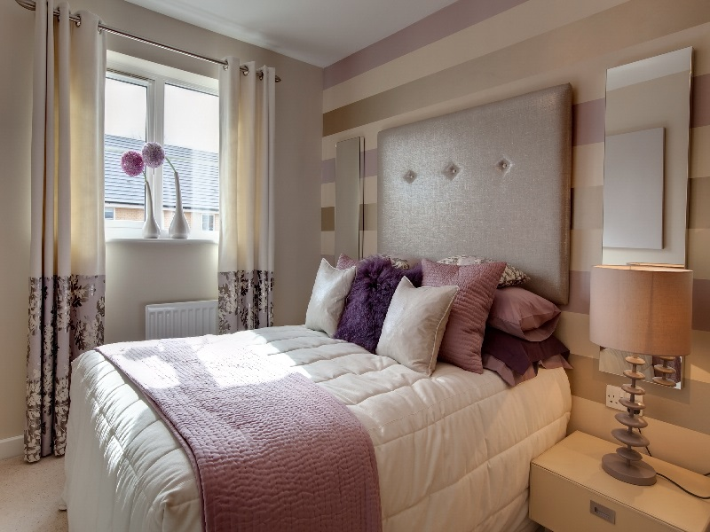 Quarto branco com pequenos detalhes em rosa na cama de casal