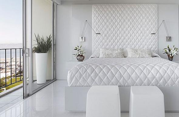 Quarto branco com varanda para casaias com lindos pufs nos pé da cama