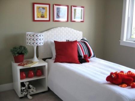 Quarto com decoração branca na cama e almofadas vermelhas para complementar