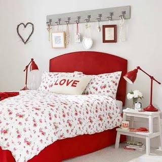 Quarto com lençois branco e cama vermelha com enfeites