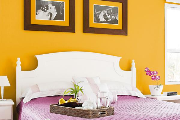 Quarto de casal com parede da cama em amarelo forte e lençois rosas