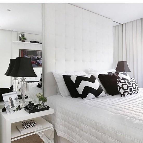 Quarto de casal com paredes brancas e com almofdas variada para divertir