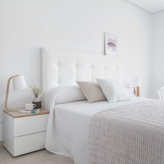 Quarto de casal com paredes brancas e roupas de cama tambpem em barnco