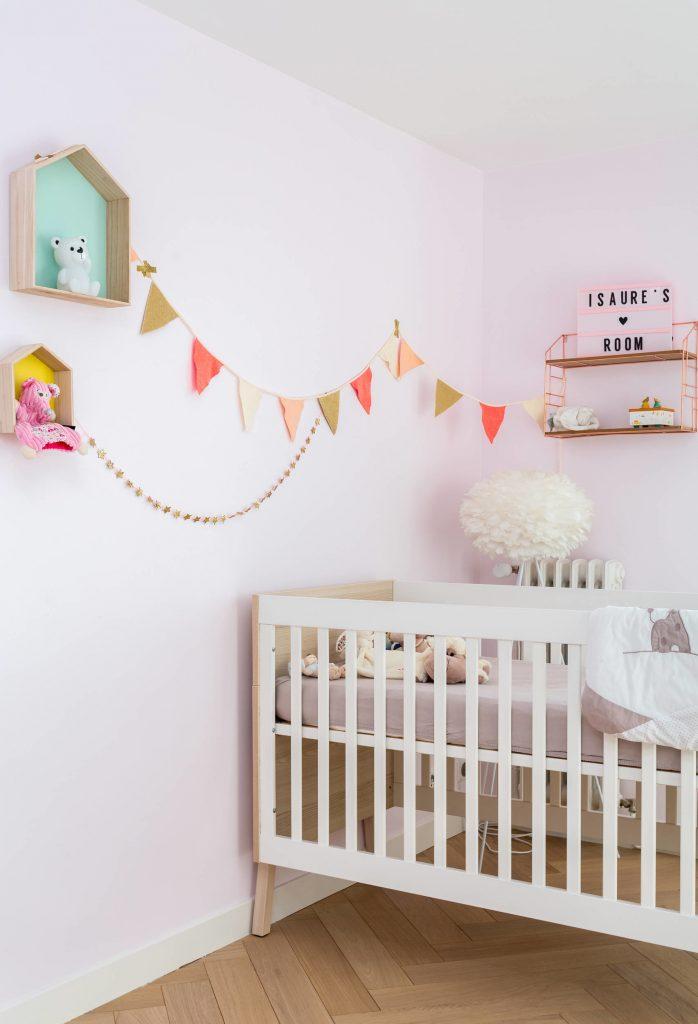 Parede branca colocada em um quarto de bebe com bandeirinhas