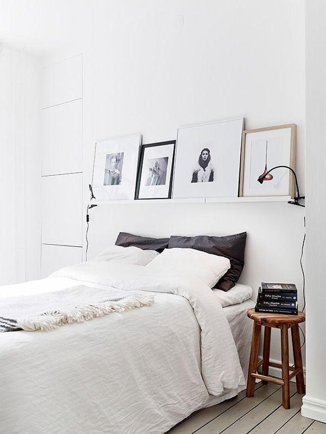 Parede decorada com quadros escorados na cor branca
