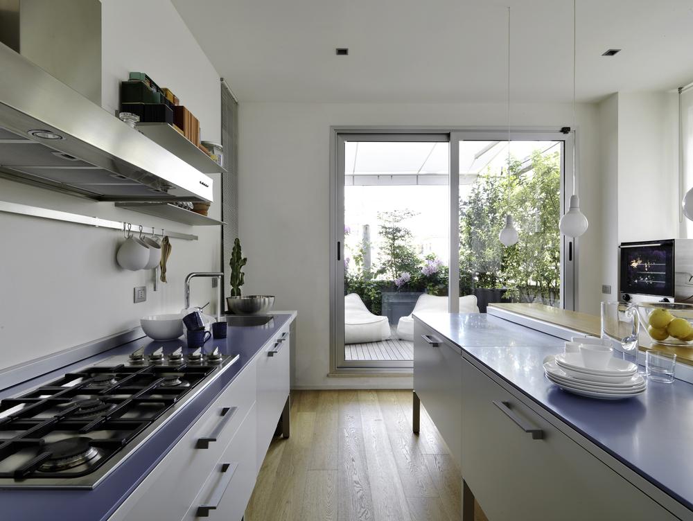 cozinha com uma porta externa de correr em vidro com moldura