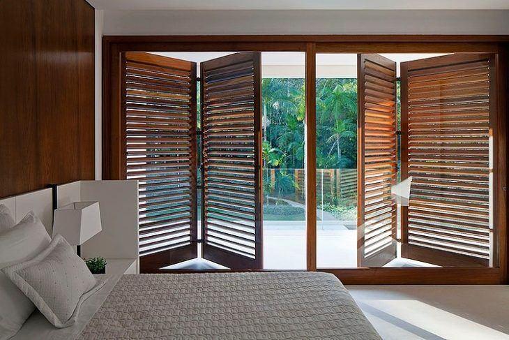 porta janela de vidro para quarto com folhas de madeira