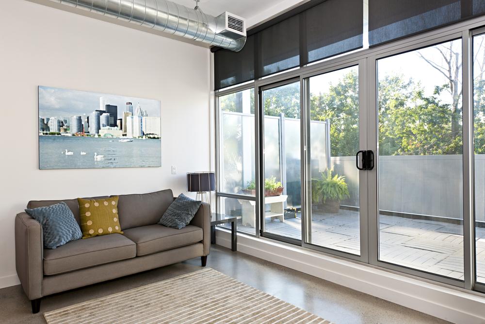 um sala comum com um sofá e sua grande porta de vidro