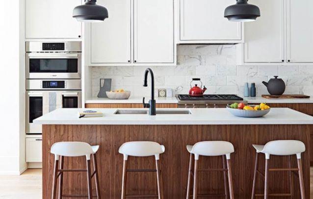 Cozinha americana com balcão no meio e bancos brancos