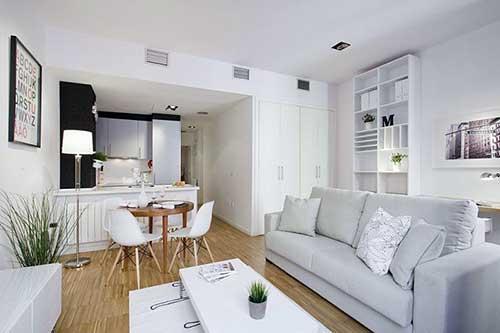 Cozinha americana com sala pequena e sofá branco