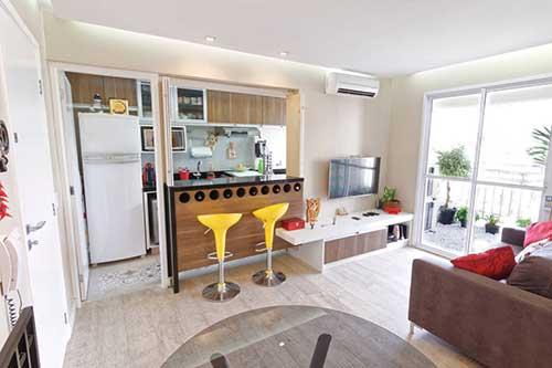 Cozinha americana em conjunto com sala e bancos amarelos