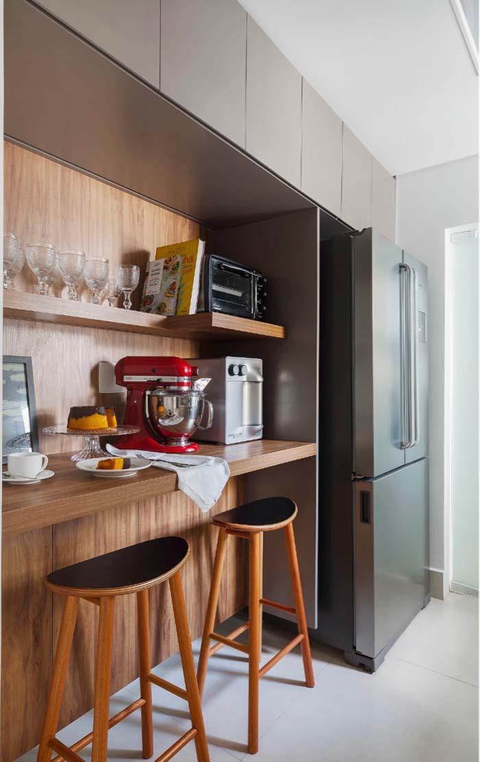cozinha americana com uma mesa embutida no balcao de madeira