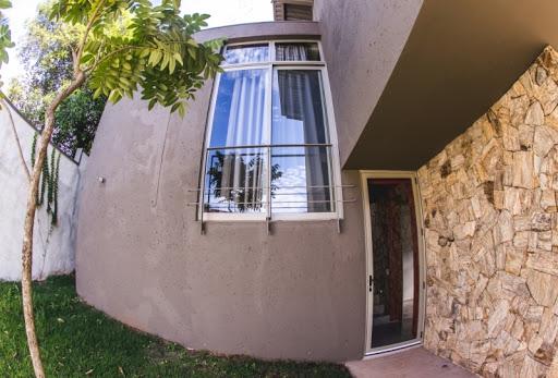 janela grande com grades e folhas de aluminio