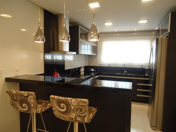 luminarias prateadas suspensa em cima do blacao da cozinha