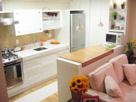 sofá rosa na sala pequena em conjunto com cozinha americana