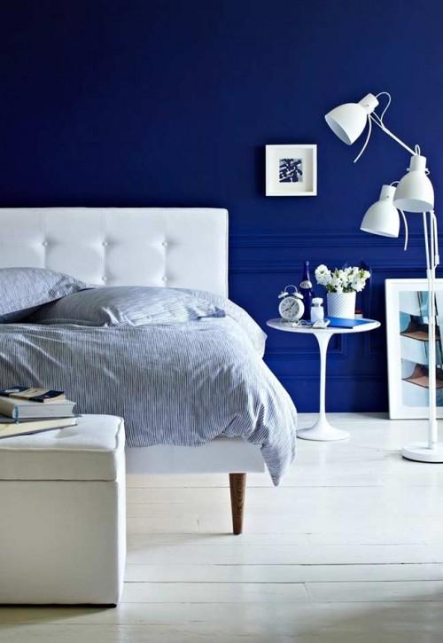 Paredes em azul marinho e piso em branco no quarto