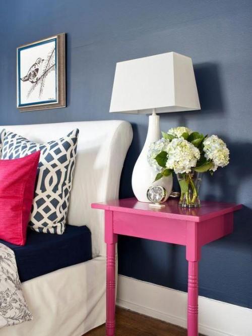 Pintura em azul marinho e movel em rosa no quarto